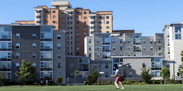 Man throwing a frisbee with dorm buildings in the background