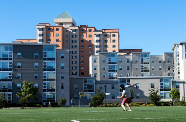 Man playing soccer with dorm buildings in the background