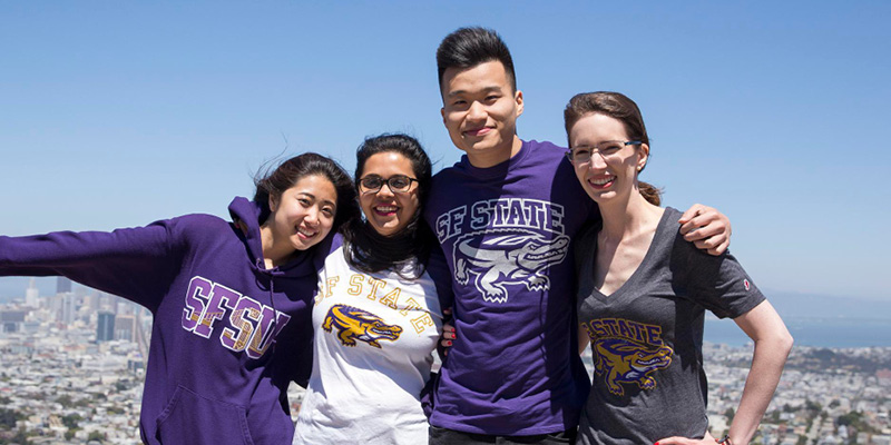 Four Students smiling in front of the San Francisco cityscape wearing SFSU apparel