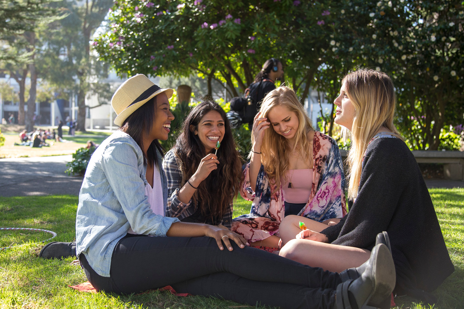 Four female students chatting on the grass
