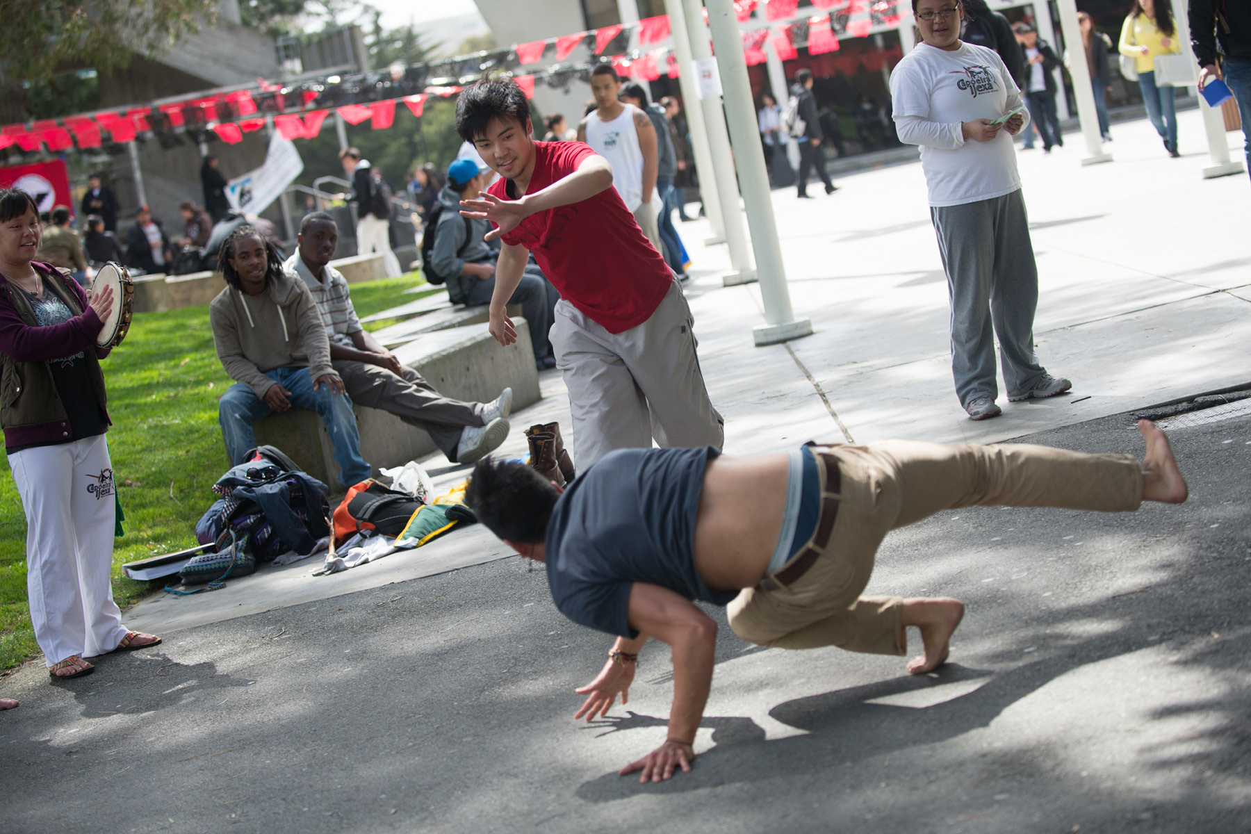 Two male students break-dancing by the Quad