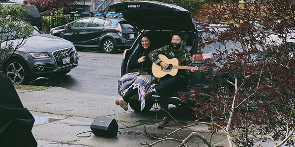 two people sitting on their trunk, singing and playing a guitar