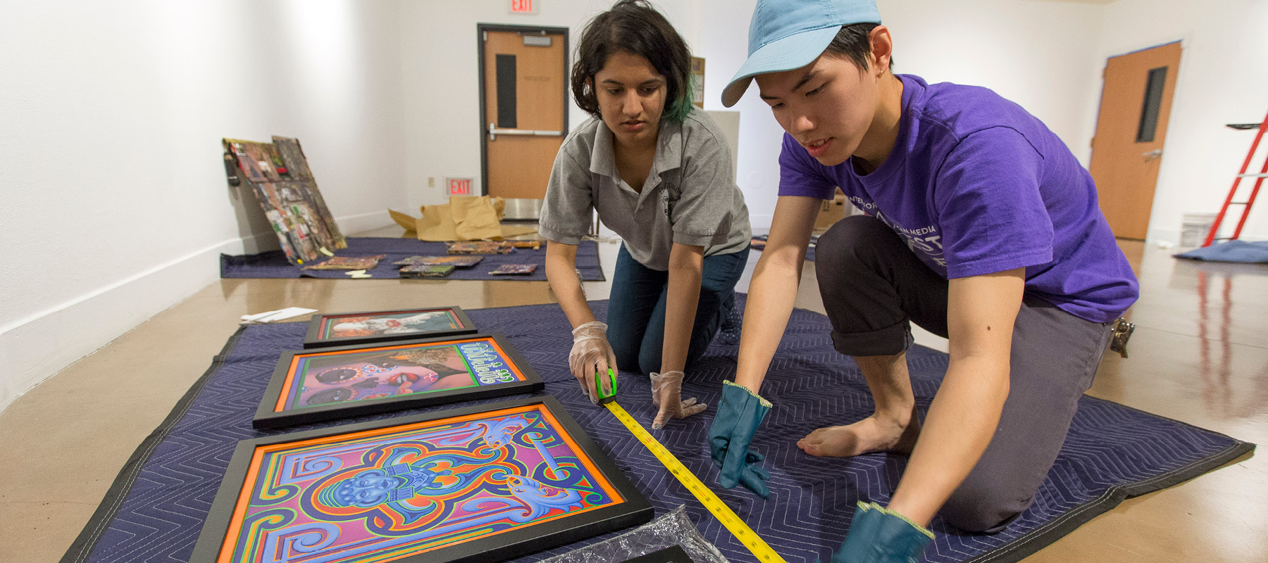 Assistant manager Aparna Dhole and gallery assistant Anh Bui install an exhibition that's part of the 50th anniversary celebration of Project Rebound.